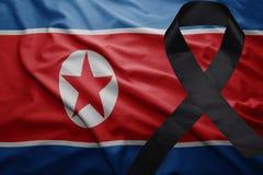 Flagge von Nordkorea mit schwarzem Trauerband Stockbild