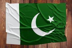 Flagge von Pakistan auf einem Holztischhintergrund Geknitterte Draufsicht der pakistanischen Flagge lizenzfreies stockbild