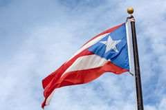 Flagge von Puerto Rico auf bewölktem Hintergrund Lizenzfreies Stockbild