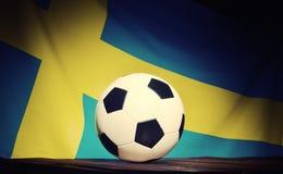 Flagge von Schweden mit Fußball auf hölzernen Brettern Lizenzfreies Stockfoto
