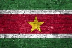 Flagge von Surinam über einem alten Backsteinmauerhintergrund, Oberfläche stockfotografie
