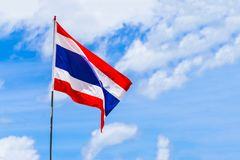 Flagge von Thailand auf roten weißen horizontalen Streifen des Fahnenmasts entwickelt sich gegen einen Hintergrund des hellen Him lizenzfreie stockfotos