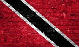 Flagge von Trinidad und Tobago über einem alten Backsteinmauerhintergrund, Oberfläche lizenzfreie stockbilder