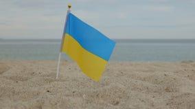 Flagge von Ukraine, stehend im Sand, vor dem hintergrund des Meeres lizenzfreie stockfotos