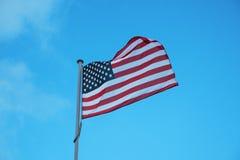 Flagge von USA, die in Wind auf Hintergrund des blauen Himmels wellenartig bewegen Lizenzfreie Stockfotos