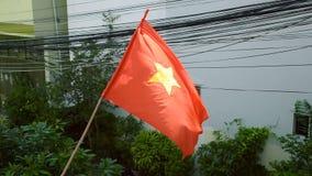 Flagge von Vietnam wellenartig bewegend vor Gebäude stock video