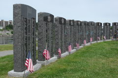 Flagged memorials. Veterans memorial stones marked with american flags at heritage park in lewiston maine royalty free stock photos