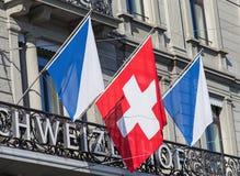 Flaggen auf der Schweizerhof-Hotel-Gebäudefassade Lizenzfreie Stockfotografie