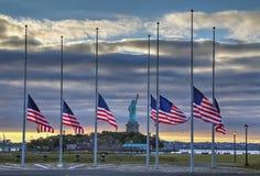 Flaggen auf Halbmast vor Freiheitsstatuen stockfotografie