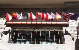 Flaggen des kleinen Landes auf einem Hotelfenster Lizenzfreies Stockfoto