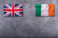 Flaggen des Vereinigten Königreichs und des Irlands auf konkretem Hintergrund Stockfotografie