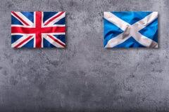Flaggen des Vereinigten Königreichs und des Schottlands auf konkretem Hintergrund Stockfotografie