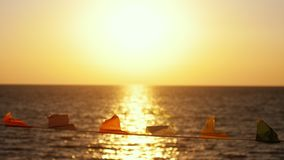 Flaggen entwickeln sich im Wind vor dem hintergrund des Meeres auf dem Strand während des Sonnenuntergangs Stockfotografie