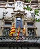 Flaggen unter spanischer Uhr Stockfotografie