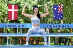 Flaggen von Dänemark und von Australien, die vom schönen sexy Mädchen gehalten wird Lizenzfreie Stockfotos