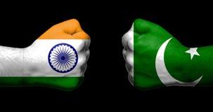 Flaggen von Indien und von Pakistan gemalt auf zwei geballten Fäusten, die auf schwarzem Hintergrund-/Indien- - Pakistan-Beziehun stockfotos