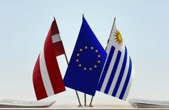 Flaggen von Lettland EU und von Uruguay lizenzfreie stockfotos