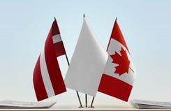 Flaggen von Lettland und von Kanada lizenzfreie stockbilder