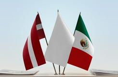 Flaggen von Lettland und von Mexiko lizenzfreies stockbild