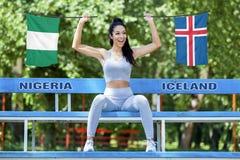 Flaggen von Nigeria und von Island, die vom schönen sexy Mädchen gehalten wird stockfotos