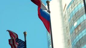Flaggen von Russland und von Vereinigten Staaten auf Hintergrund des blauen Himmels stock video