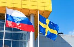 Flaggen von Schweden und von Russland, die gegen IKEA-Speicher wellenartig bewegen Lizenzfreies Stockbild
