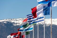 Flaggen von verschiedenen Ländern mit Bergen im Hintergrund Stockbild