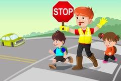 Flagger y niños que cruzan la calle Imagen de archivo