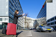 Flagging a cab. A businessman with several suitcases flagging a taxi Stock Photography
