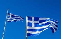 Flaggor av det Grekland flyget i vind och blå himmel Arkivbilder