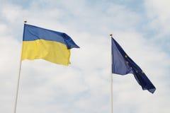 Flaggor av europeisk union och Ukraina som vinkar på flaggstång som isoleras på vit bakgrund Royaltyfri Fotografi