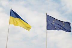 Flaggor av europeisk union och Ukraina som vinkar på flaggstång som isoleras på vit bakgrund Royaltyfria Bilder