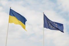 Flaggor av europeisk union och Ukraina som vinkar på flaggstång som isoleras på vit bakgrund Fotografering för Bildbyråer