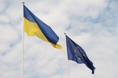 Flaggor av europeisk union och Ukraina som vinkar på flaggstång som isoleras på vit bakgrund Arkivfoto