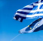 Flaggor av Grekland och europeisk union på bakgrund för blå himmel, politik av Europa royaltyfri bild