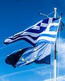 Flaggor av Grekland och europeisk union p? bakgrund f?r bl? himmel, politik av Europa royaltyfria bilder