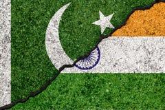 Flaggor av Indien och Pakistan målade på sprucken väggbakgrund stock illustrationer