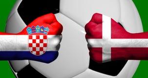Flaggor av Kroatien och Danmark som målades på två, grep hårt om nävar som vänder mot sig med fotbollbollen för closeupen 3d i ba Royaltyfria Foton