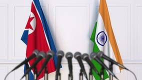 Flaggor av Nordkorea och Indien på det internationella mötet eller konferensen framförande 3d Royaltyfri Fotografi