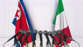 Flaggor av Nordkorea och Italien på det internationella mötet eller konferensen framförande 3d Royaltyfria Bilder