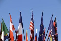 Flaggor av olika länder med blå himmel som bakgrund fotografering för bildbyråer