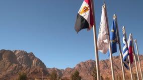 Flaggor av olika länder på en bakgrund av berg stock video