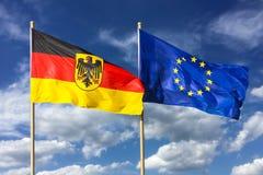 Flaggor av Tyskland Förbundsrepubliken Tyskland; i tysk: Bundesrepublik Deutschland och EU för europeisk union som vinkar i vind Arkivbilder