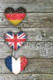 Flaggor av Tyskland, Frankrike och England på en träbakgrund Arkivfoton