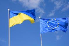 Flaggor av Ukraina och för europeisk union EU mot den blåa himlen Royaltyfri Bild