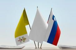 Flaggor av Vatican City och Slovenien med en vit flagga i det middleUnited kungariket av Storbritannien Royaltyfria Bilder