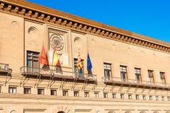 Flaggor av Zaragoza, Spanien, Aragon och den europeiska unionen nära byggnaden av stadshuset av Zaragoza, Spanien royaltyfri foto