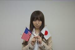 Flaggor för amerikan och för japan för affärskvinna hållande Royaltyfri Fotografi