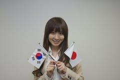 Flaggor för korean och för japan för affärskvinna hållande Arkivbilder