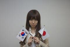 Flaggor för korean och för japan för affärskvinna hållande Royaltyfri Foto